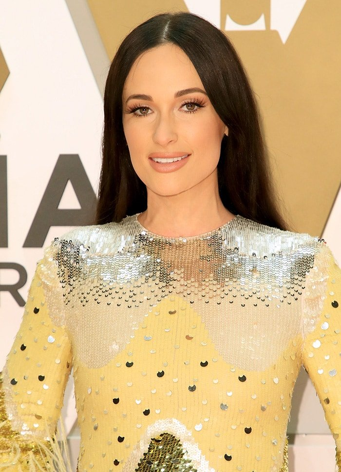 Kacey Musgraves wears her long black hair down pin straight and off-the-shoulder