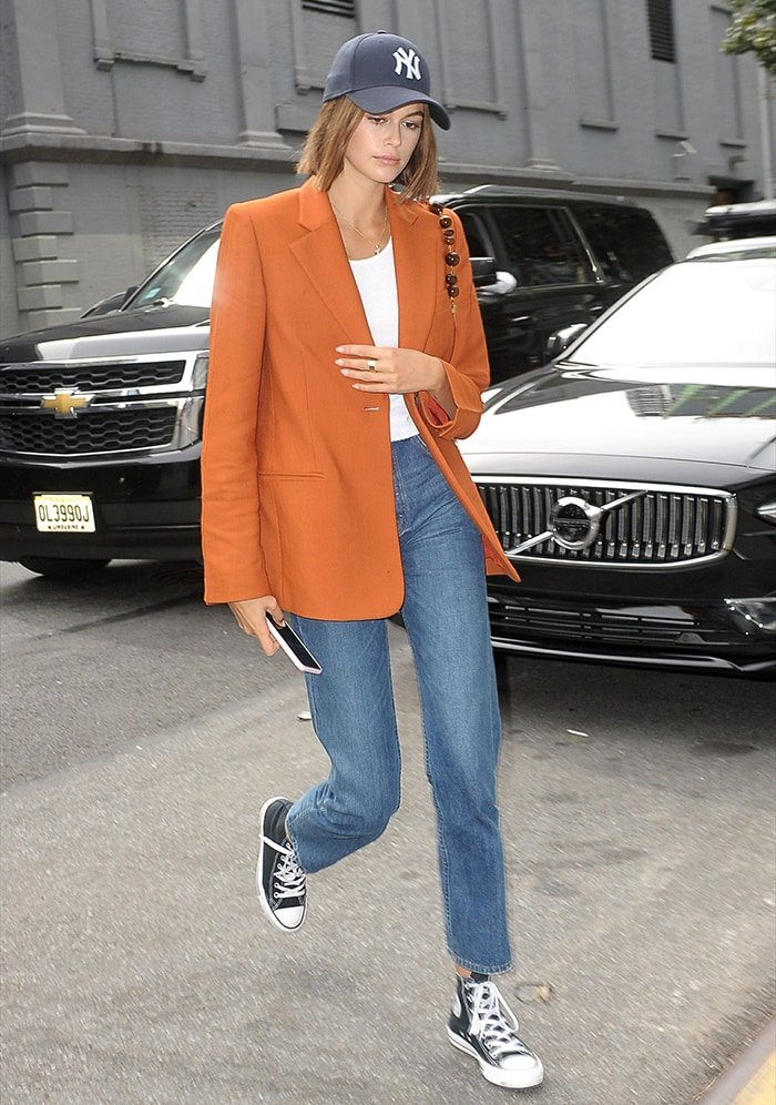 Kaia Gerber teams her black Converse All Star High Tops with an orange blazer, jeans, and baseball cap while out in New York City on September 5, 2019