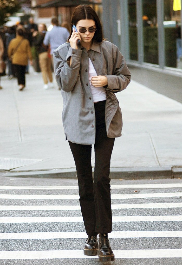 Kendall Jenner teams her Dr. Martens boots with gray jacket, white top, and black pants