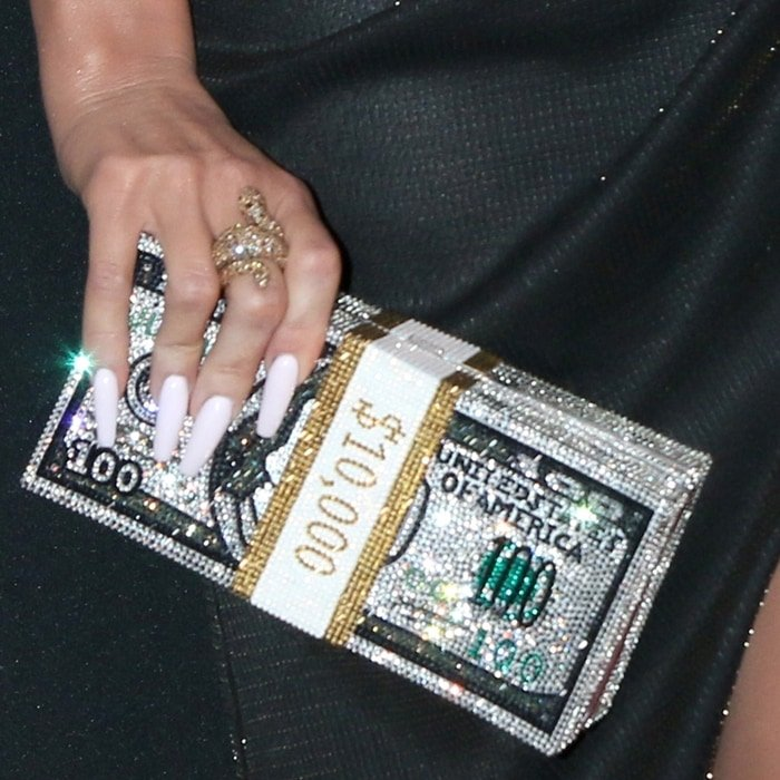 Khloe Kardashian's dazzling bag is rendered in colorful handset crystal and features a 24 karat gold plated money wrap detail in glowing aurum crystal