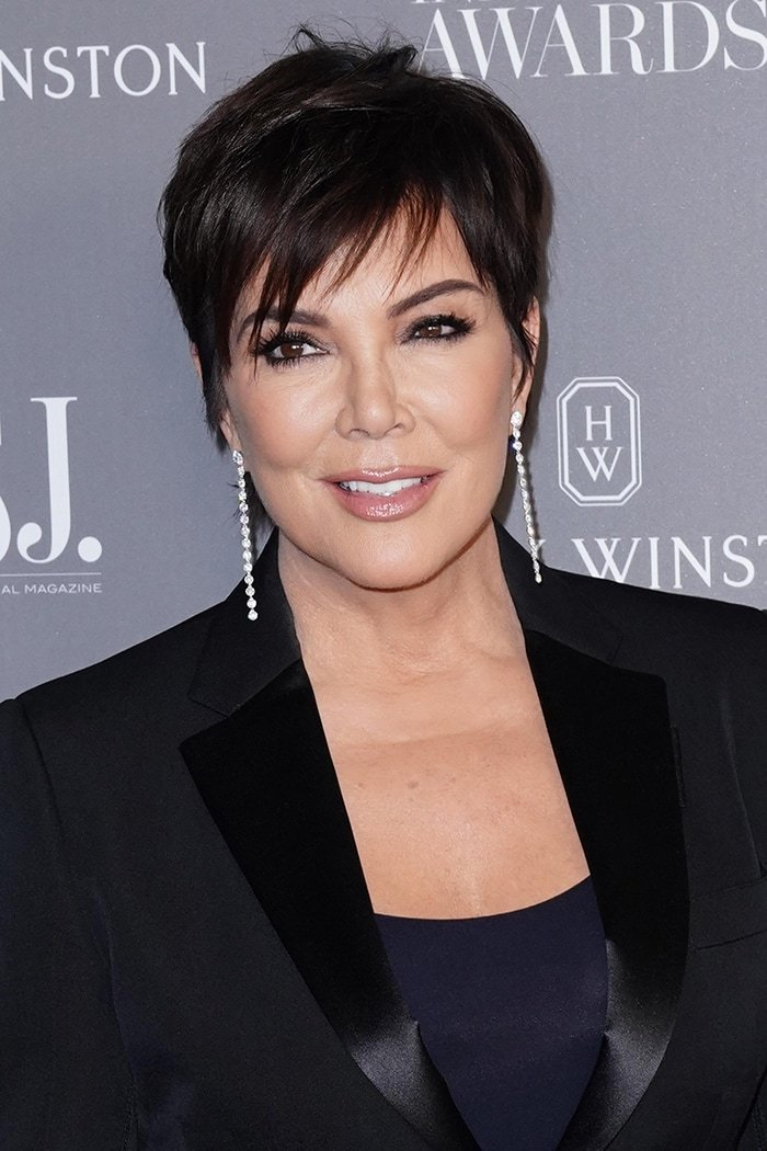 Kris Jenner wears mussed pixie haircut and dark eyeliner, mascara, and nude lipgloss