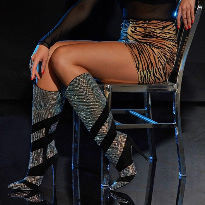 A mid-calf rhinestone-embellished boot featuring a stiletto heel, pointed toe, and zipper closure
