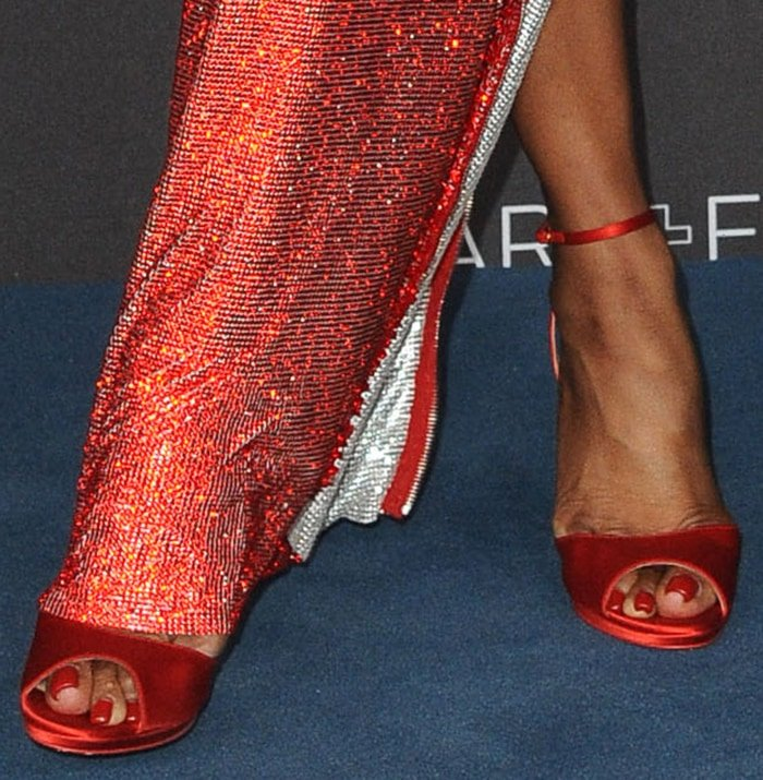 Naomi Campbell finishes off her head-to-toe red look with Christian Louboutin sandals