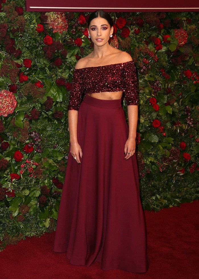 Naomi Scott looks holiday-ready in a red Miu Miu embellished crop top and skirt