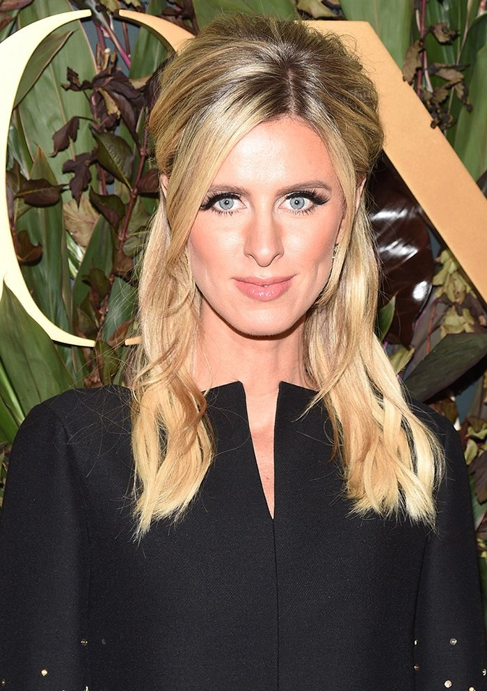 Nicky Hilton styles her blonde hair in half-up style and accentuates her blue eyes with false lashes