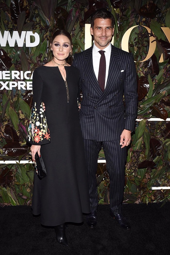 Olivia Palermo poses with her husband Johannes Huebl on the WWD Honors black carpet