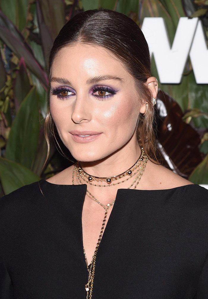 Olivia Palermo pulls her hair back into a ponytail and wears purple eye-makeup