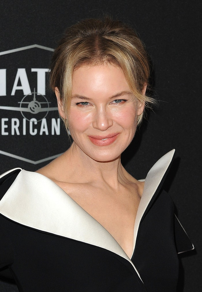 Renee Zellweger styles her blonde hair in a chic updo and wears soft pink makeup