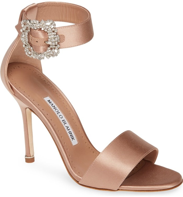 Bejeweled buckle ornamentation sparkles at the ankle of an elegant satin sandal that takes you through the event season in style