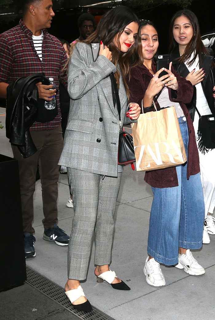 Selena Gomez takes pictures with fans outside the iHeartRadio Studios