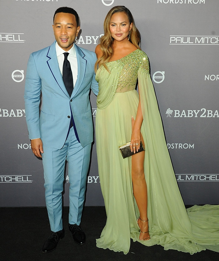 John Legend wears a blue suit as he joins Chrissy Teigen on the black carpet at the Baby2Baby Gala 2019