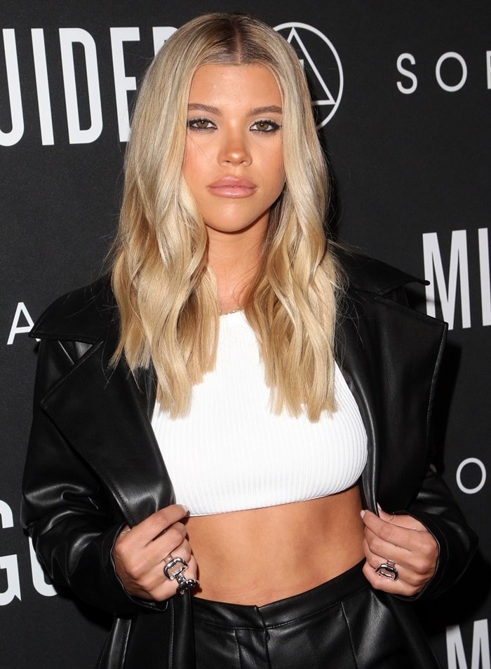 Sofia Richie's white rib bandage crop top and a trench coat