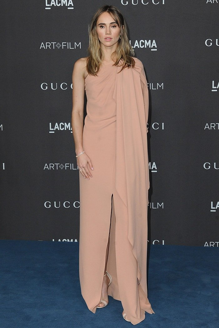 Suki Waterhouse keeps it simple but classy in a Gucci one-shoulder drape dress
