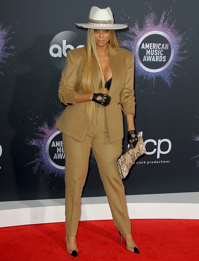 Tyra Banks flaunts major cleavage in Don Murphy pantsuit