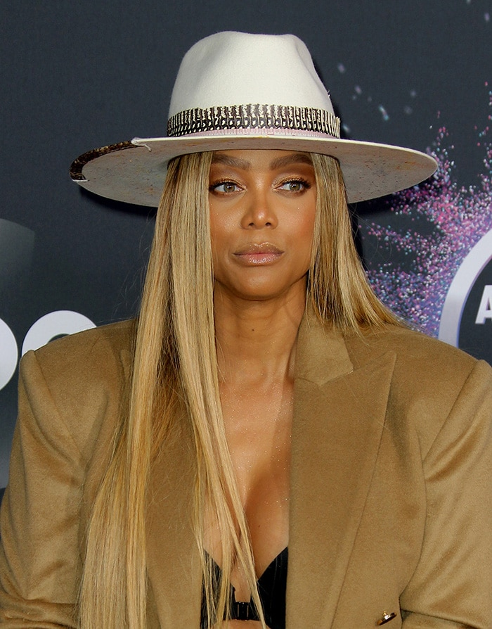 Tyra Banks wears a waist-length wig and shimmery makeup