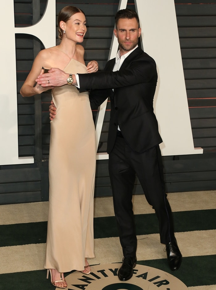 Adam Levine holds his hand over Behati Prinsloo's chest to hide a nip slip at the 2015 Vanity Fair Oscar Party