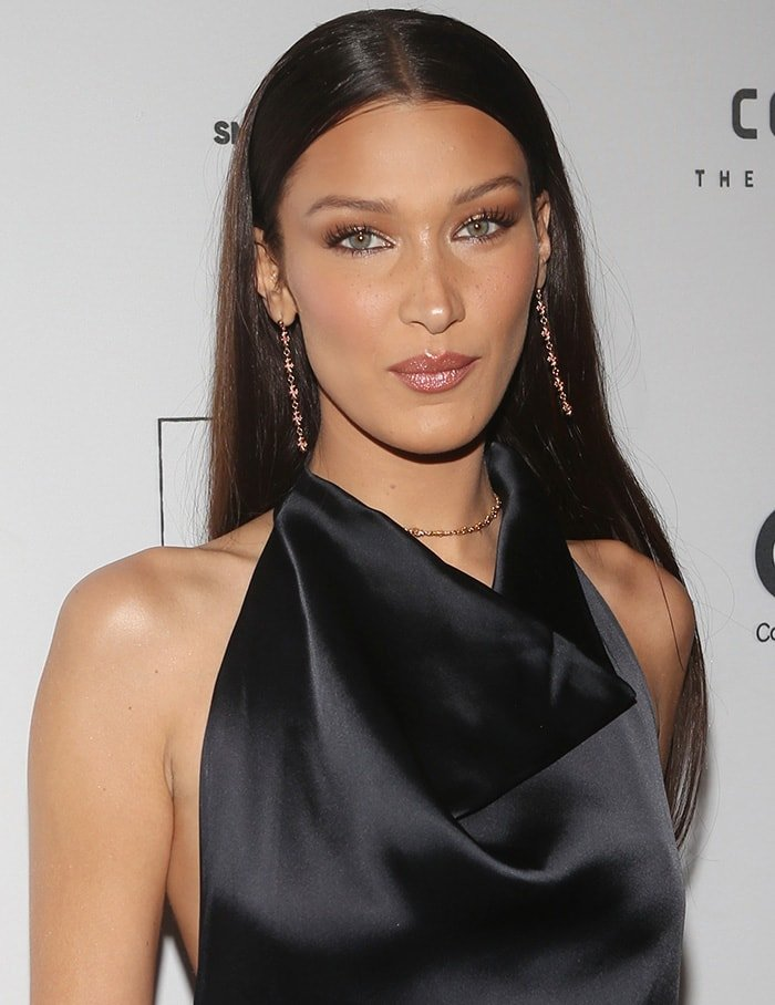 Bella Hadid wears extensions and accentuates her features with shimmering eyeshadow, mascara, and peachy pout