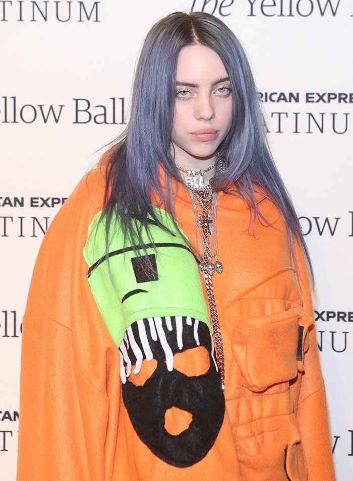 Billie Eilish in an orange hoodie at Pharrell Williams' Yellow Ball event on September 10, 2018
