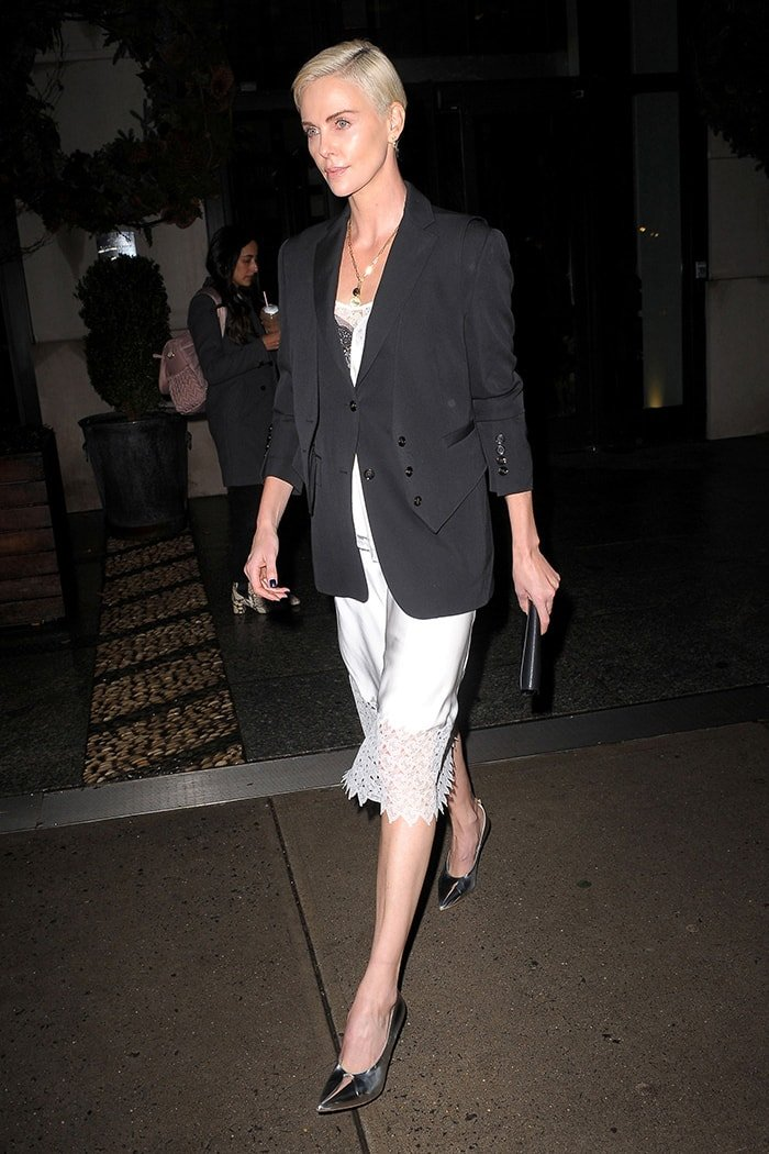 Charlize Theron in a Riccardo Tisci Burberry white slip dress and black blazer