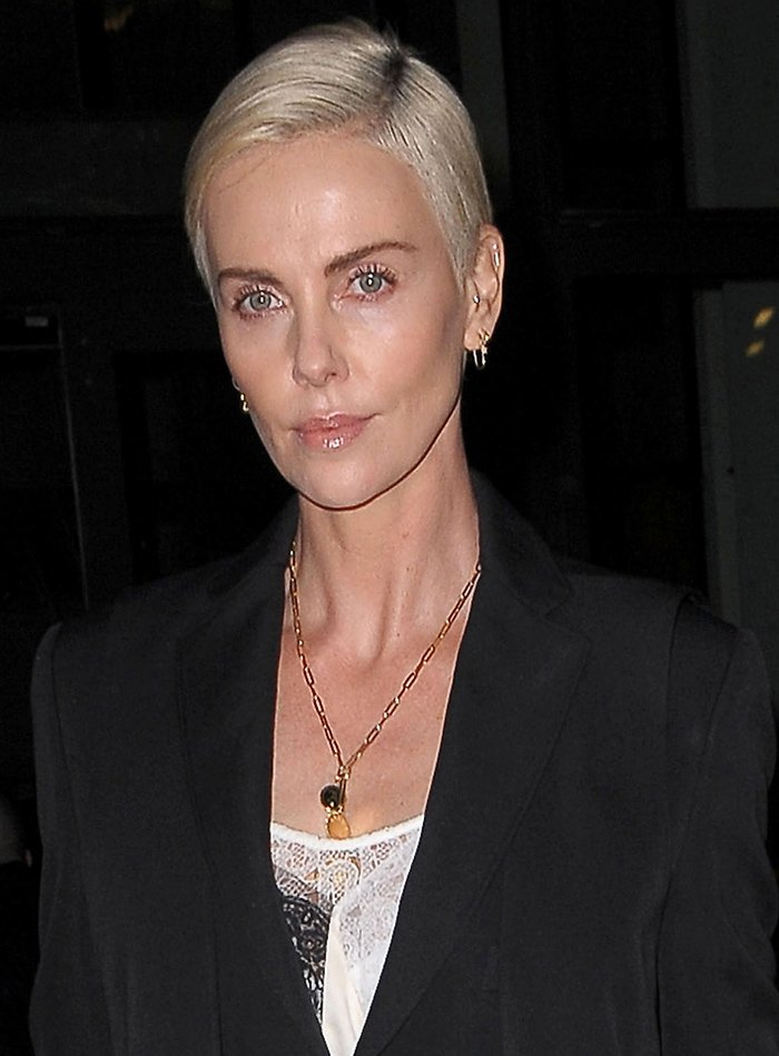 Charlize Theron wears a side-parted blonde pixie with nude lip gloss