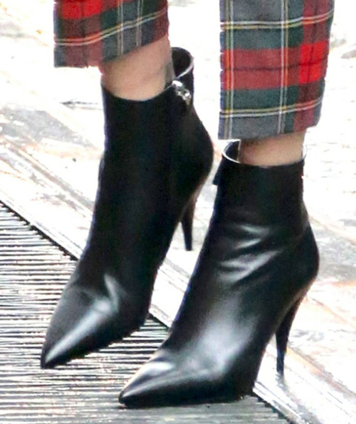 Charlize Theron teams her cropped tartan pants with black pointed-toe boots