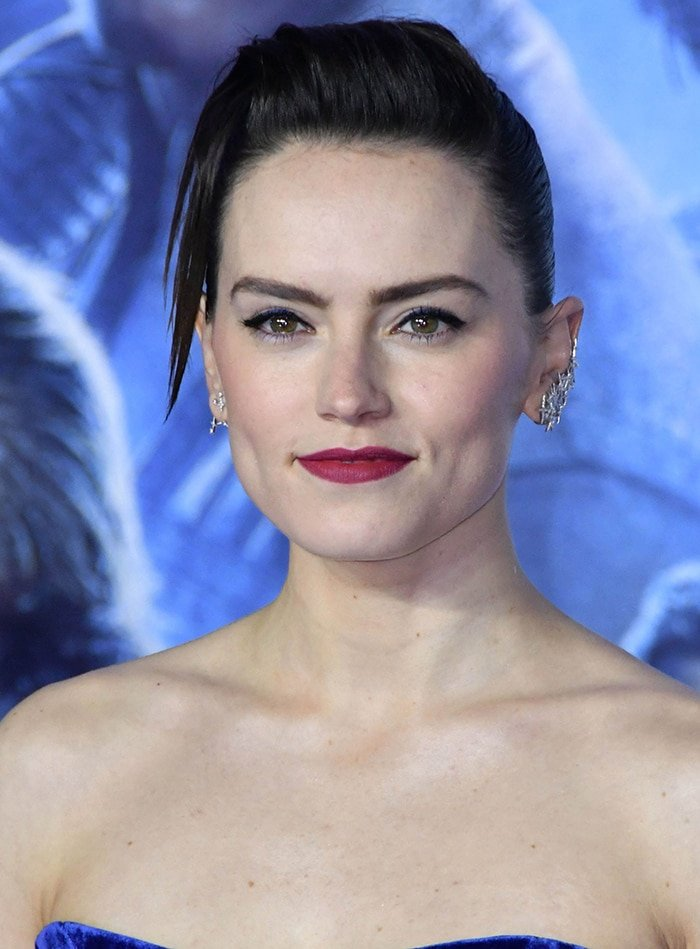 Daisy Ridley wears a slicked back hairstyle with blue tinge winged eyeliner and plum lipstick