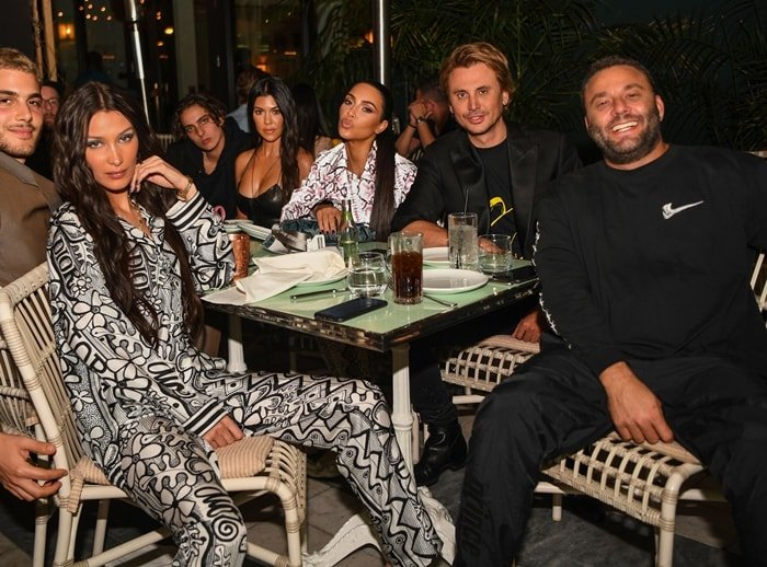 LIV nightclub owner David Grutman smiling with Bella Hadid, Kourtney Kardashian, Jonathan Foodgod Cheban, and Bad Bunny are seen at Swan