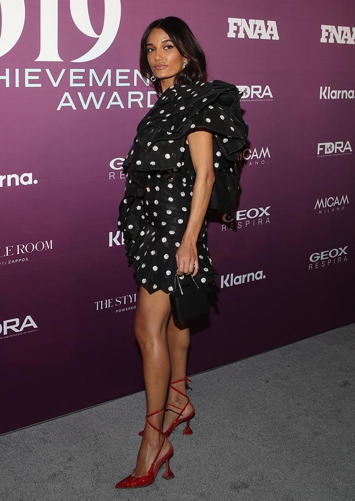 Amina Muaddi shows off her toned figure in a black polka dot mini dress