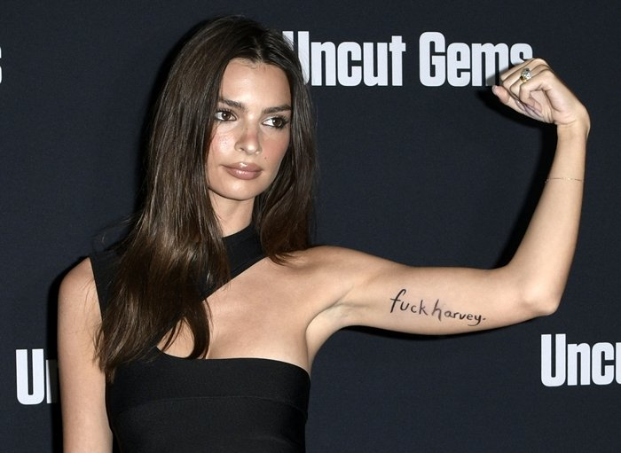 Emily Ratajkowski shows off the Fuck Harvey writing on her arm at the Uncut Gems