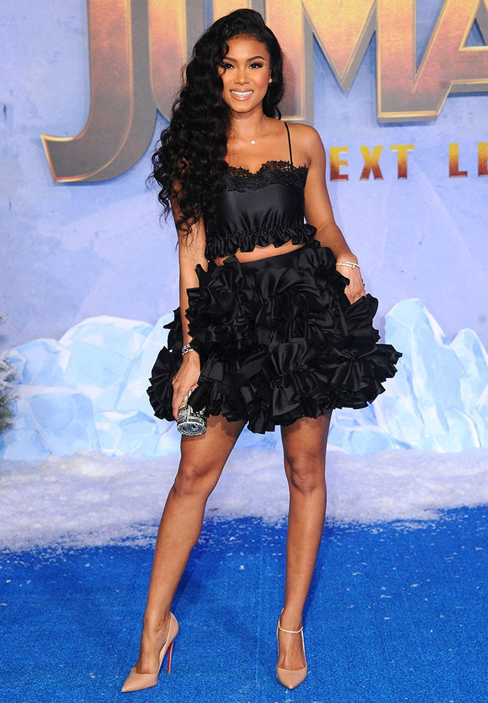 Eniko Parrish flaunts her legs in a Greta Constantine black ruffled crop top and a matching ruffled skirt