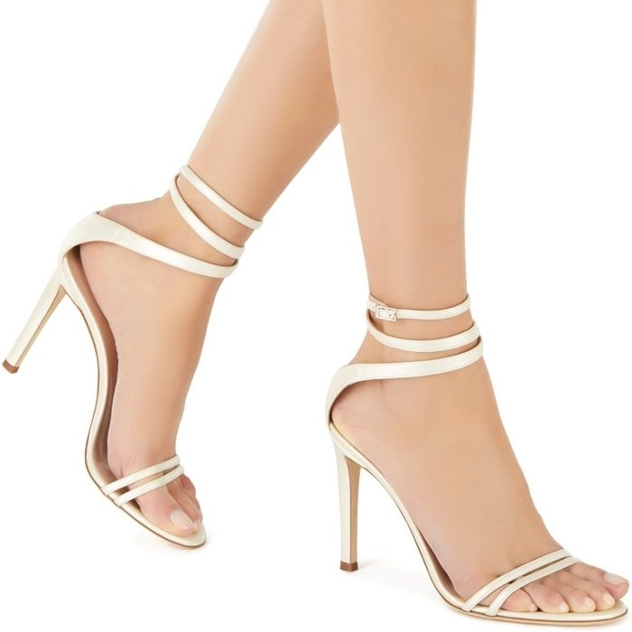 These high-heel, cream coloured patent sandals feature a front strap formed by two thinner straps and a wrap ankle strap