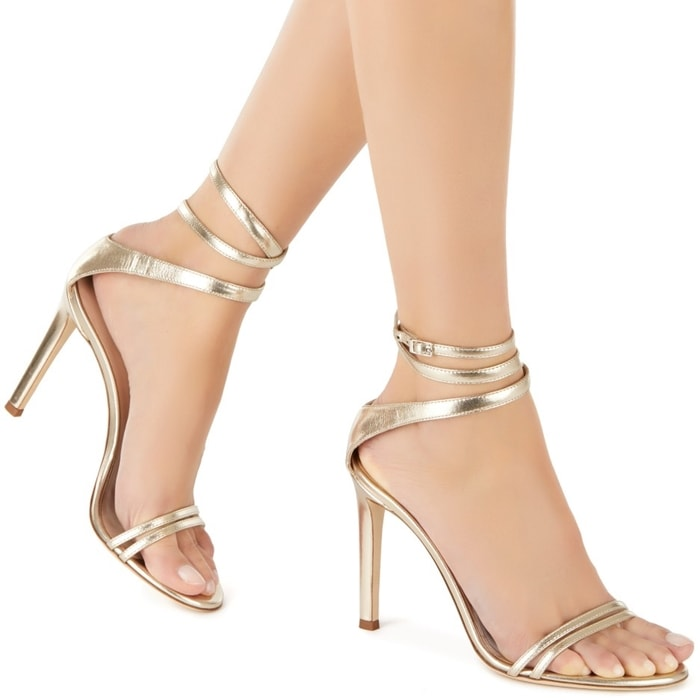 These high-heel platinum patent sandals feature a front strap formed by two thinner straps and a wrap ankle strap