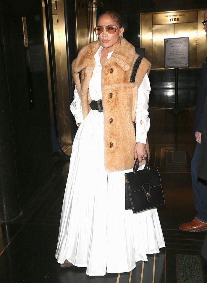 Jennifer Lopez wears a Coach shearling vest while leaving NBC Studios