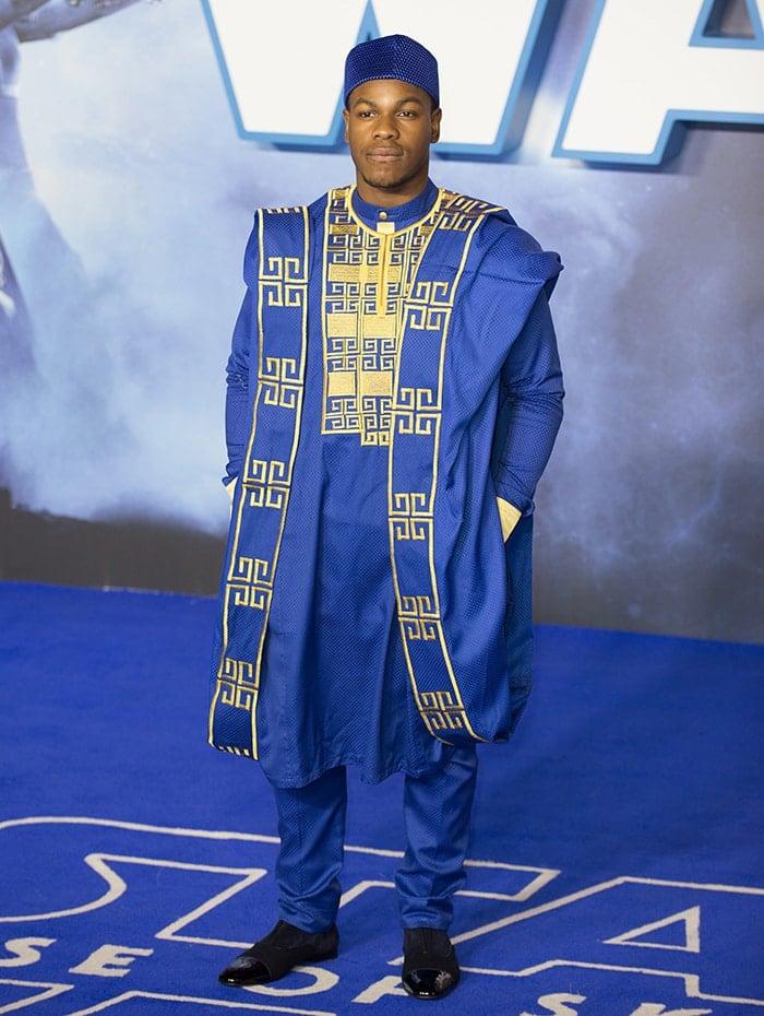 John Boyega wears a traditional Nigerian Agbada dress with Fila hat and black shoes