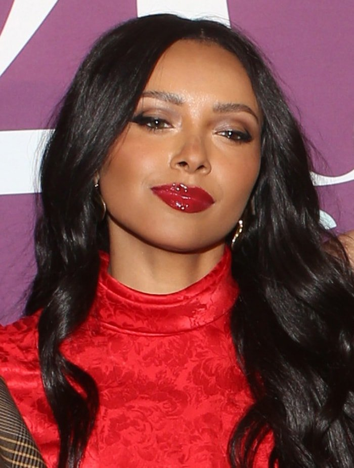 Kat Graham wears her long dark hair in loose curls with glossy red lipstick
