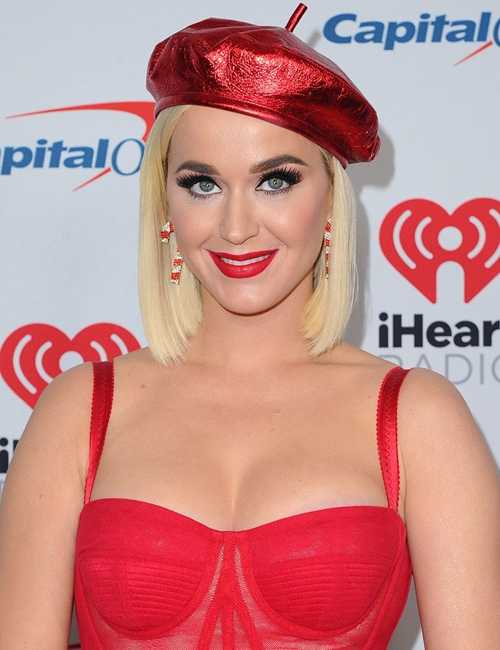 Katy Perry wears a red beret with candy cane earrings and red matte lipstick