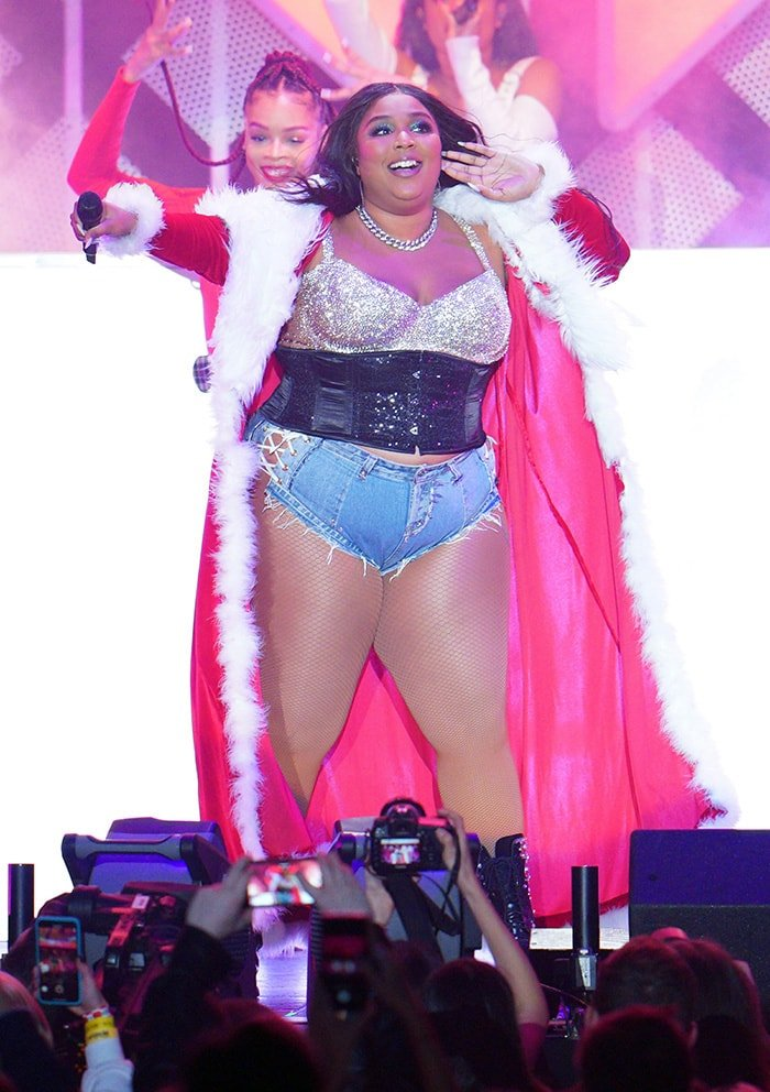 Lizzo performs in tiny denim shorts and glittery bra top with corset at the 2019 KIIS FM iHeartRadio Jingle Ball Show in Los Angeles