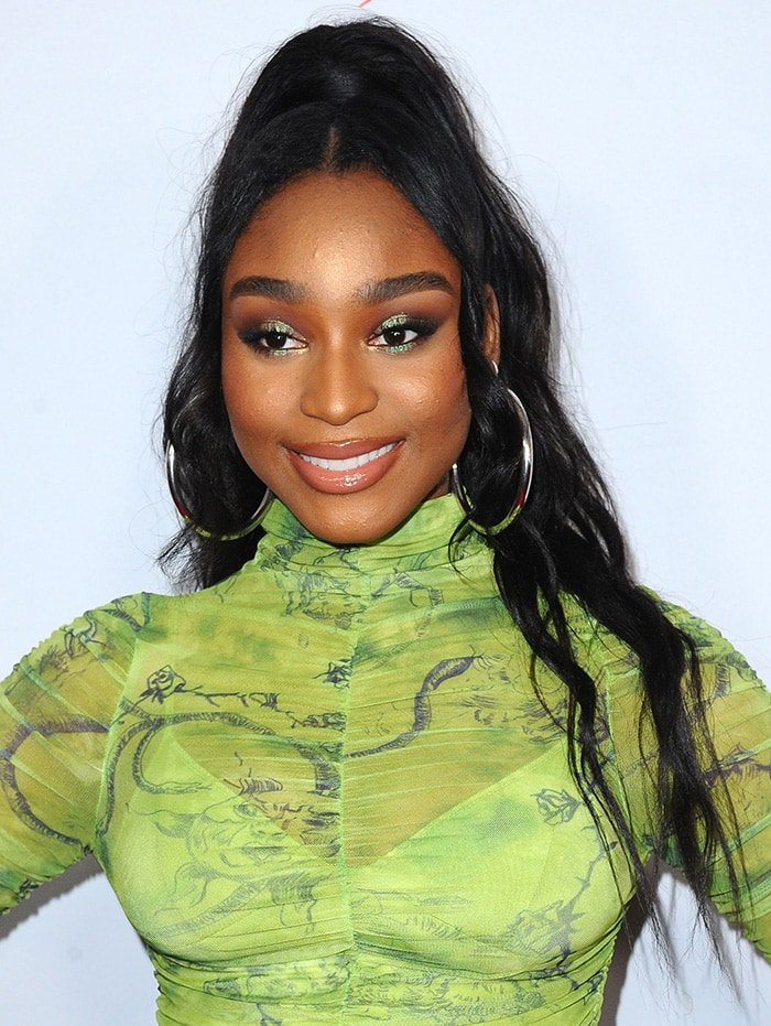 Normani wears half ponytail hairstyle with extensions and coordinating green eyeshadow