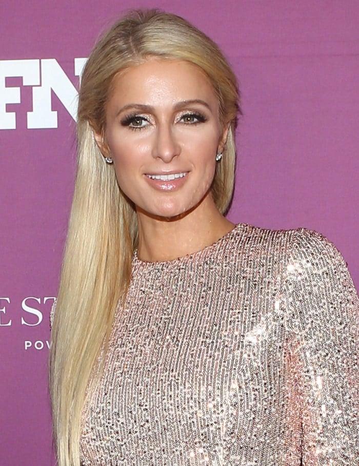 Paris Hilton styles her long blonde hair straight with glittery eyeshadow