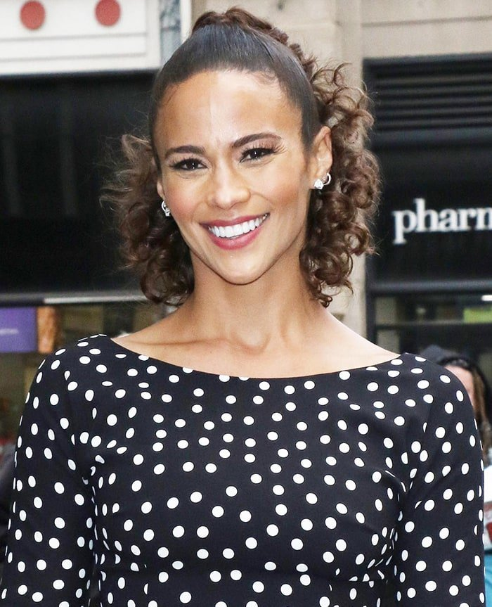 Paula Patton wears her curled hair in a ponytail with mascara and dark pink lipstick