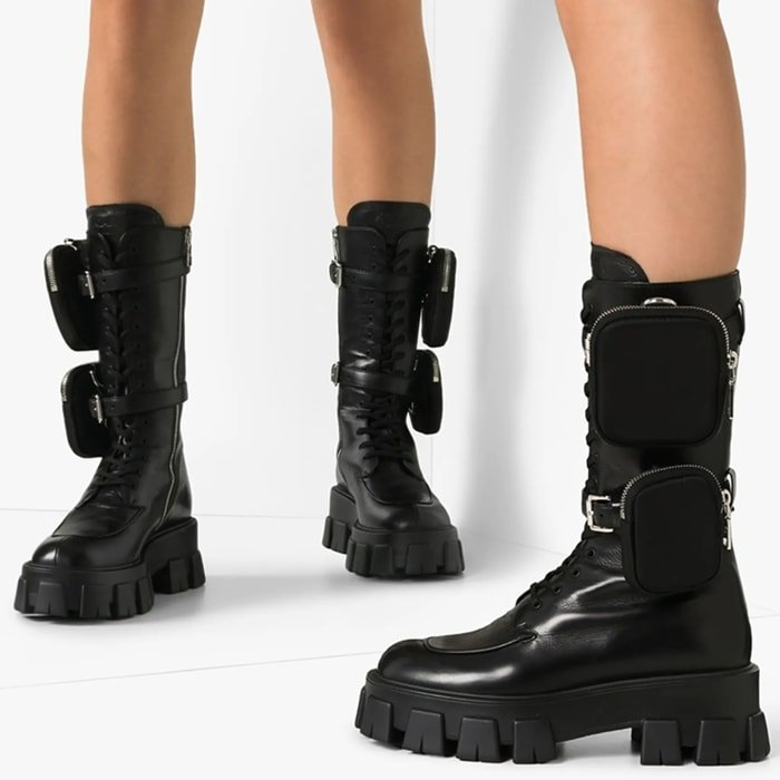 Designed in a mid-calf silhouette, this style features a round toe, lace-up front, detachable buckled straps with zipped pockets, side zip fastening and chunky tread sole