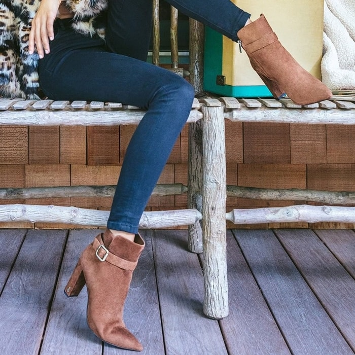 Logo hardware sets off the wrapped half-moon heel and strap of a chic Rita bootie with a pointy-toe silhouette and plenty of versatility