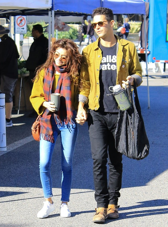 Sarah Hyland and Wells Adams walk arm-in-arm at a Los Angeles farmer's market on December 15, 2019
