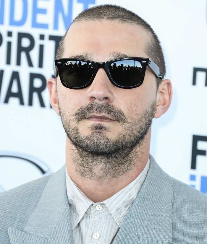 Actor Shia LaBeouf wears Ray-Ban sunglasses and a Gucci suit as he arrives at the 2020 Film Independent Spirit Awards