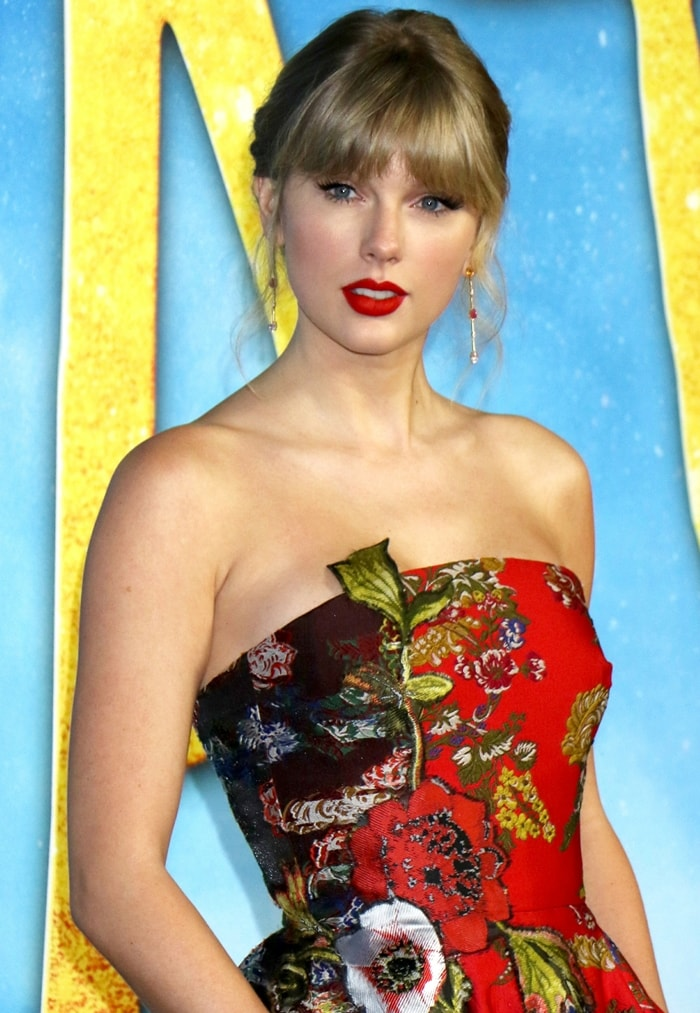 Taylor Swift with red lips shows off her Maxior drop earrings