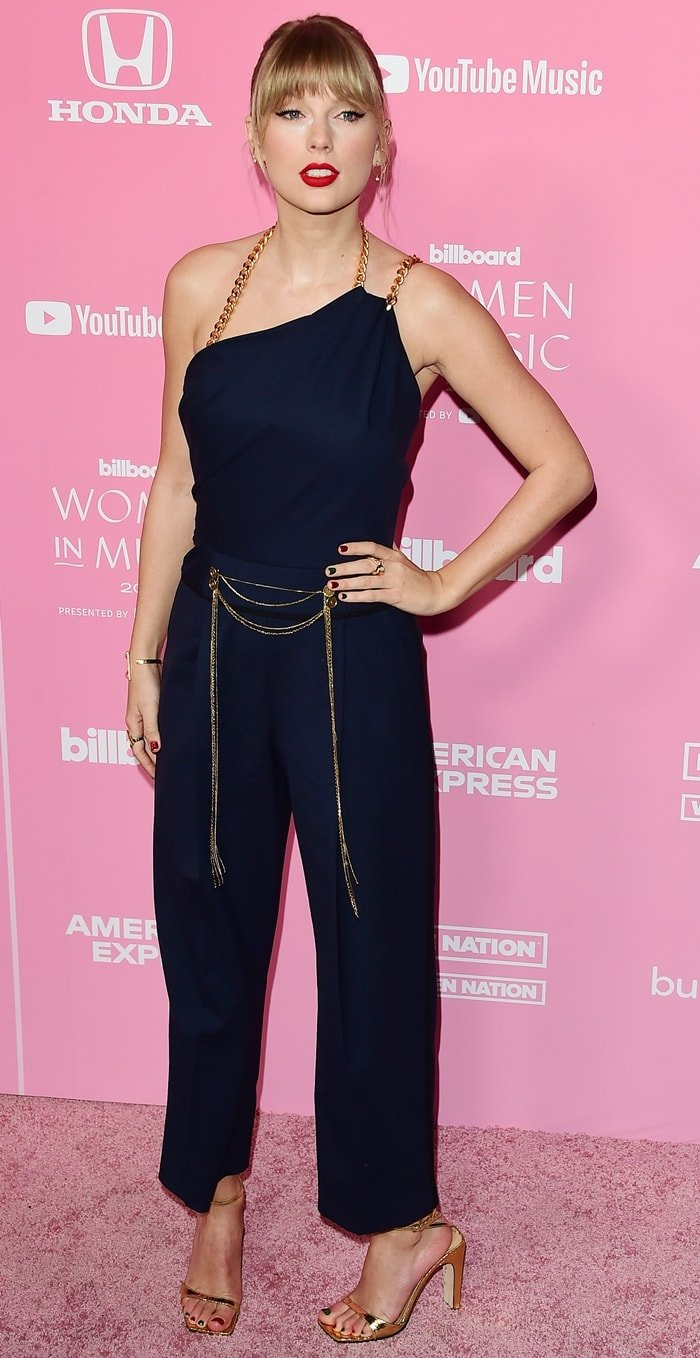 Taylor Swift's jumpsuit flaunts an asymmetric bodice that descends into relax-fit legs for a bohemian aesthetic