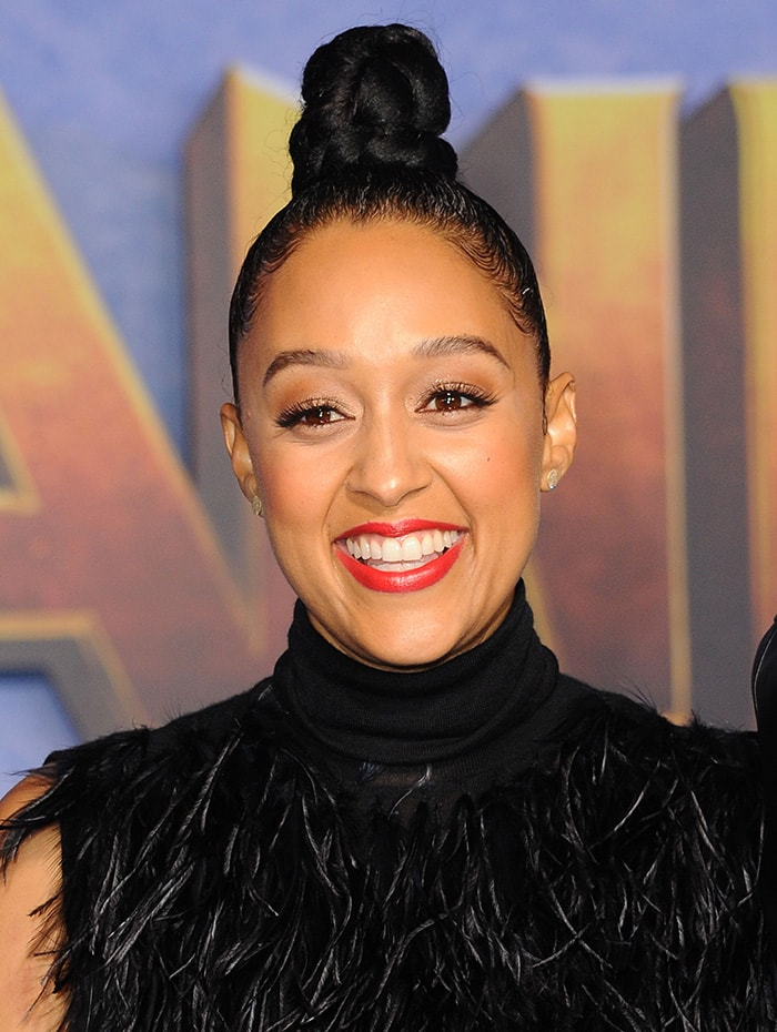 Tia Mowry pulls her hair up in a knotted bun