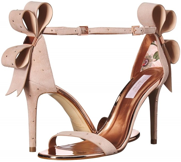 Polished studs and a dramatic bow at the heel add modern elegance to this lofty ankle-strap sandal