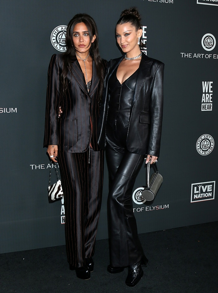Jesse Jo Stark and Bella Hadid dressed in matching black outfits at the 2020 Art of Elysium Heaven Gala held at the Hollywood Palladium on January 4, 2020