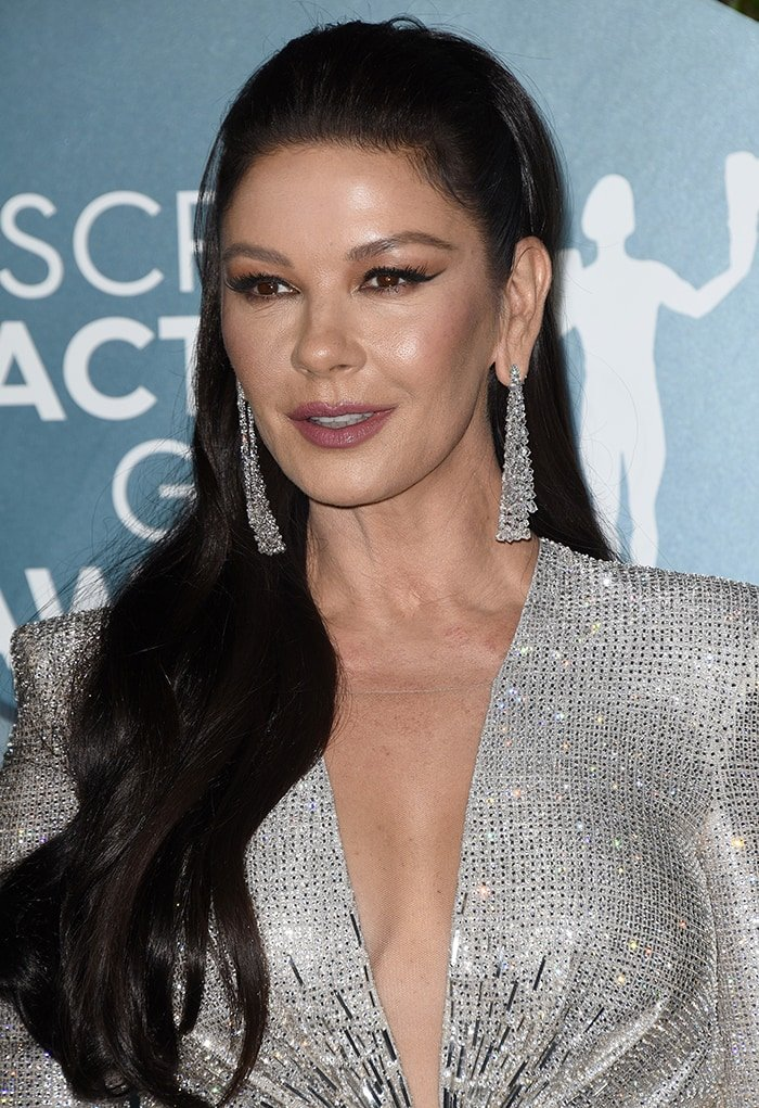 Catherine Zeta-Jones wears half-up wavy hairstyle with winged eyeliner and mauve lip shade